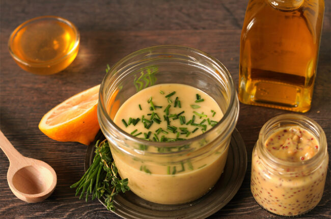 Small jar with Mustard Chive Vinaigrette, and ingredients around it