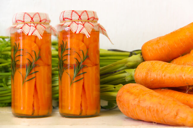 2 jars of pickled carrots and raw carrots next to them