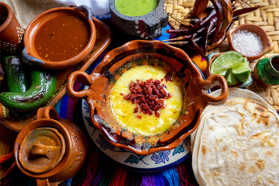 Bowl of queso in the middle of other sauces and tortillas
