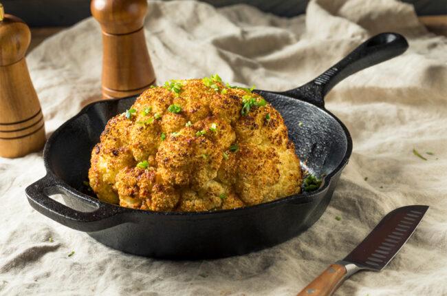 Miso Glazed Whole Roasted Cauliflower in a cast iron pan