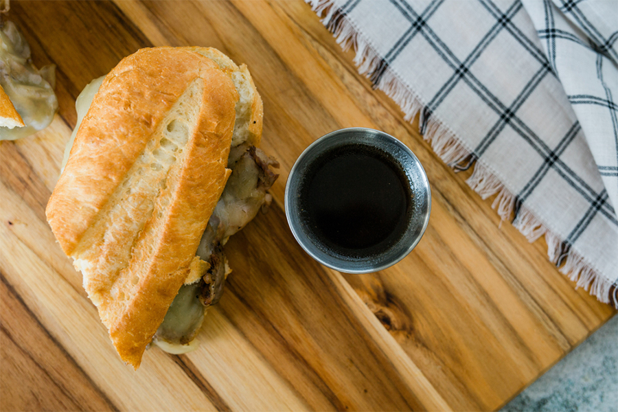 Portobello Mushroom French Dip Sandwich next to a cup of dipping sauce
