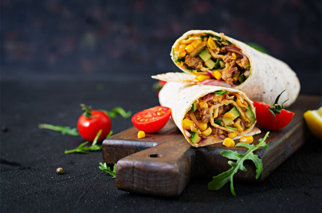 Two burritos on a cutting board