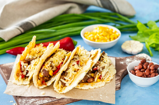 4 turkey tacos on a platter with cheese taco shells