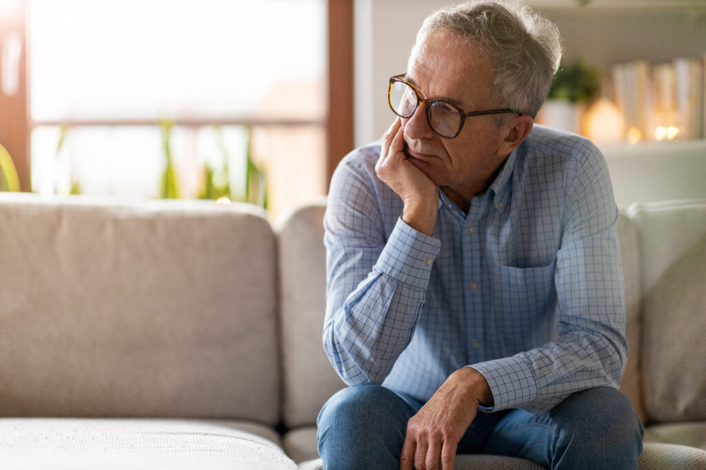Elderly man anxiously sitting on couch