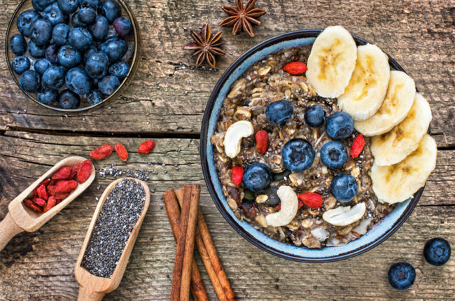 Bowl of Coconut Chia Hot Cereal with bananas, blueberries, goji berries and cashews