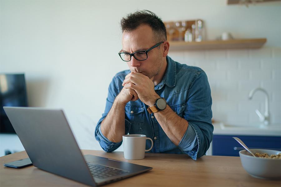 Upset man looking at laptop
