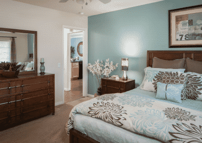 Furnished bedroom with dresser and bed and blue wall