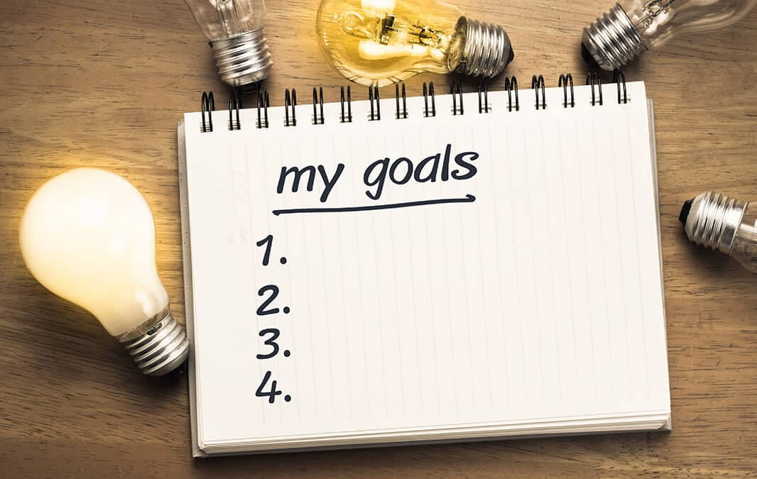 Notebook with my goals written on the front and surrounded by lightbulbs