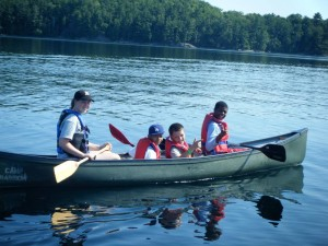 Kids enjoy canoeing on the lake.