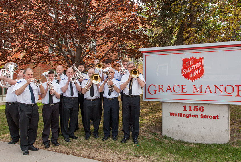 Members of the band pose with their instruments next to the Grace Manor sign.