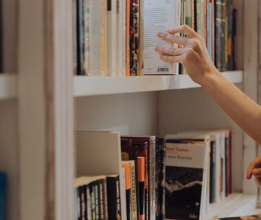 person holding white book in white wooden shelf