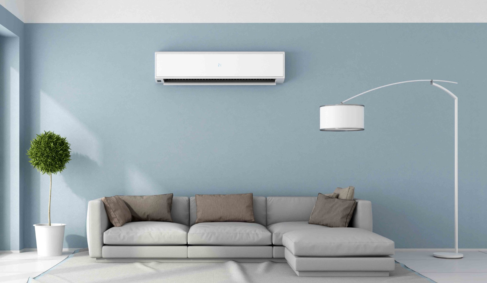 A mini-split AC unit is installed on a home's interior wall above the living room sofa.