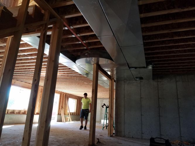 Person walking through newly constructed house frame