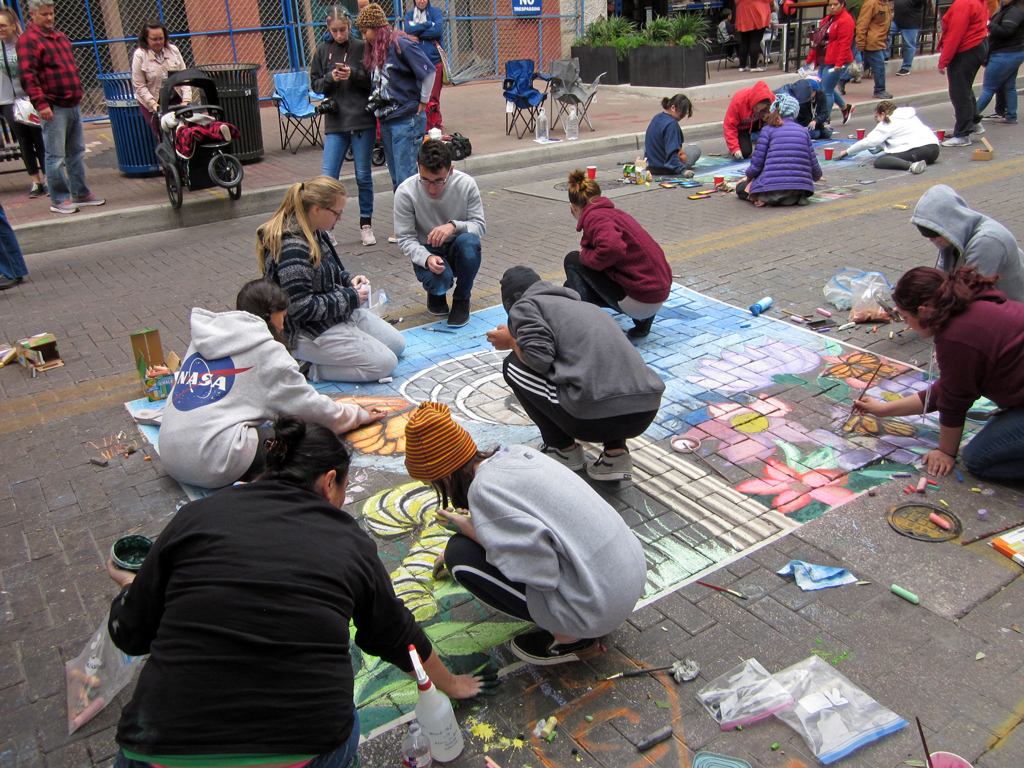 Photo of kids doing chalk art on street