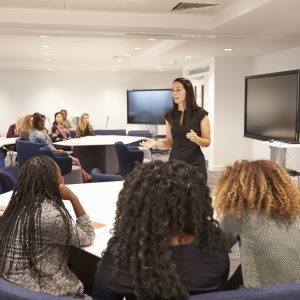 Female teacher addressing university students in a classroom