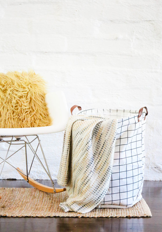 grid-patterned storage canvas bin with blanket hanging out