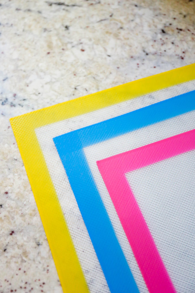 yellow, blue, and pink silicone baking mats on quartz countertop