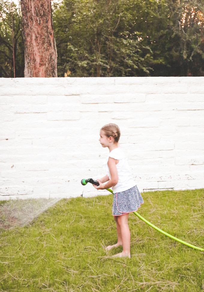 little girl holding hose