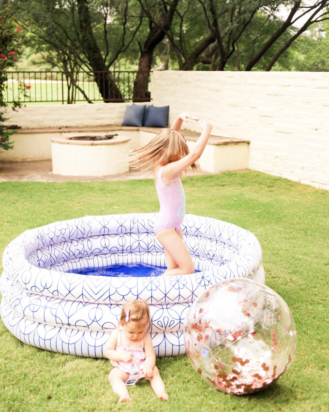 little girl twirling in swimsuit in inflatable pool