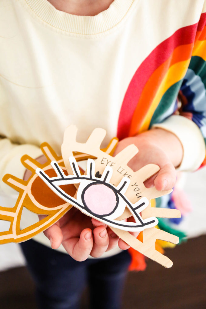 DIY wooden valentines held in the hands of a little girl