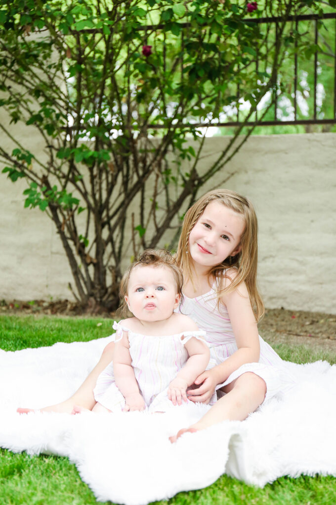 sisters sitting in easter dresses posing on grass