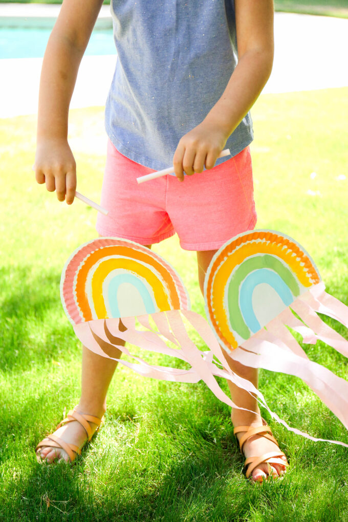 kid playing with paper plate rainbow puppets