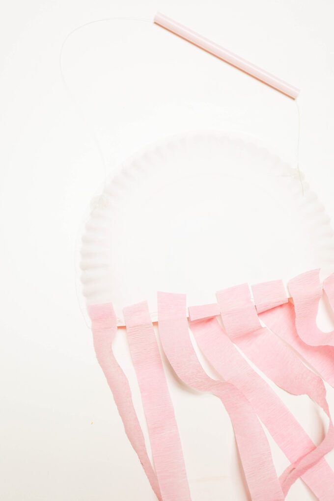 attaching tissue streamers to back of paper plate