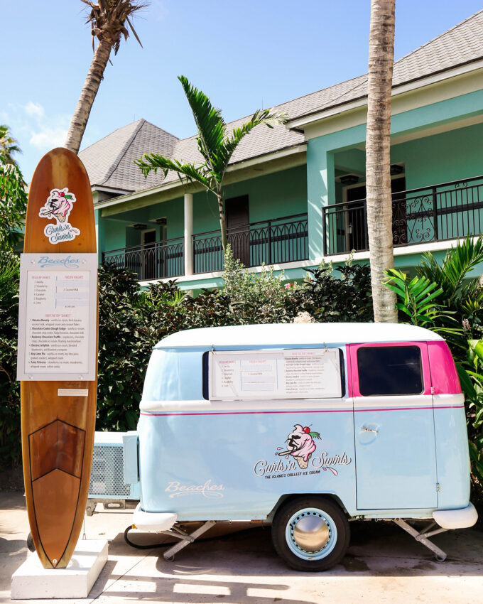 ice cream truck next to tall surf board