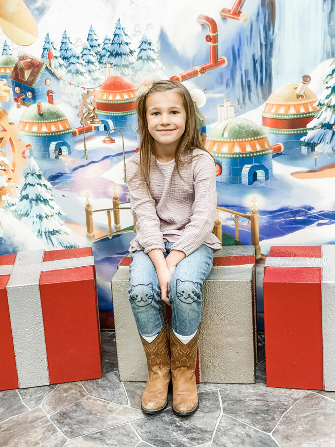 little girl posing on present box seats in santa's workshop