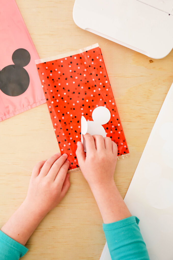 hands placing mickey sticker on favor bag