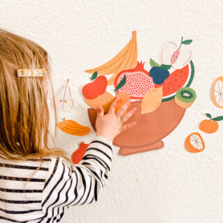 little girl placing fruit stickers on wall