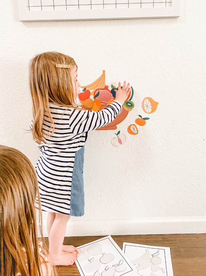 fruit stickers being placed on wall by little girl
