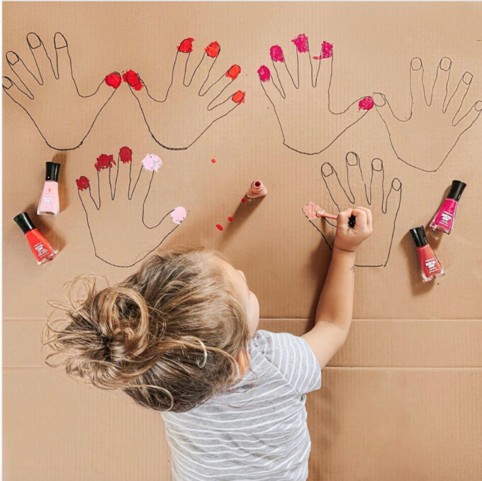 girl painting nails on cardboard