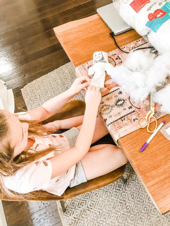 little girl stuffing homemade doll