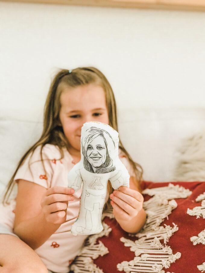 little girl holding homemade doll