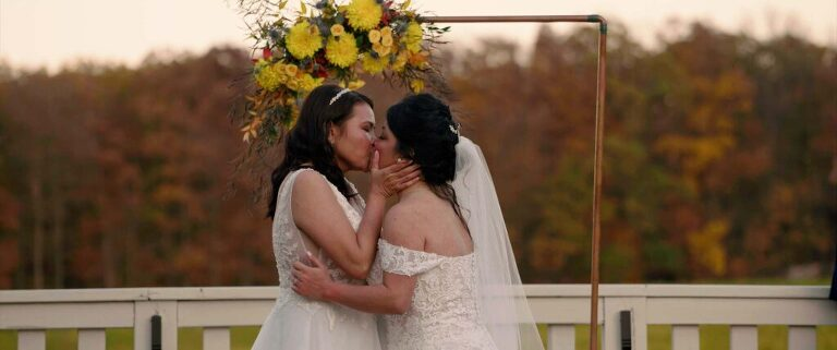 two brides first kiss at wedding ceremony