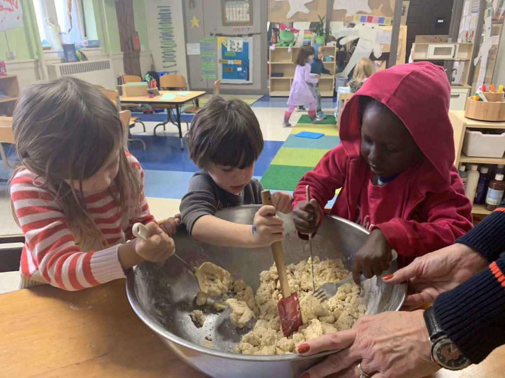 Kids stirring dough in large bowl.