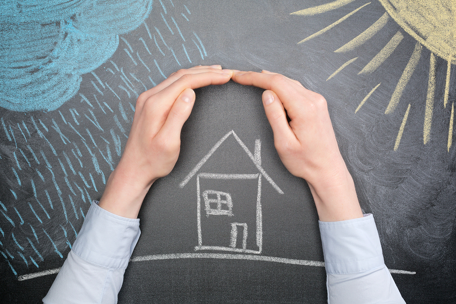 A young businesswoman protects a house from the elements - rain or storm and sun. Blackboard drawing top view.