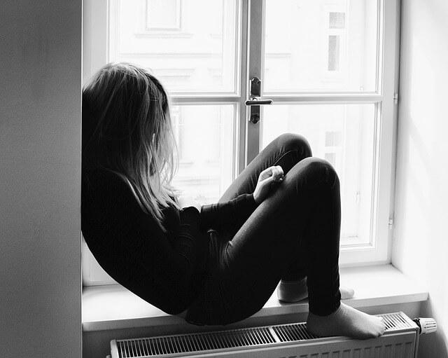 Depressed person sitting on windowsill