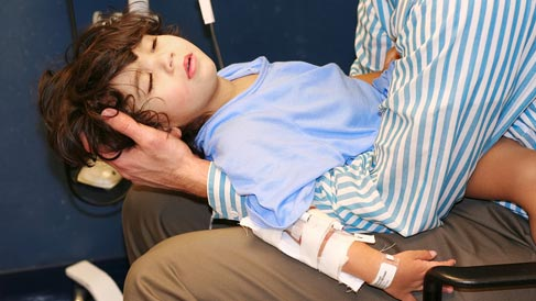 Photo of Injured Child in the Arms of a Guardian