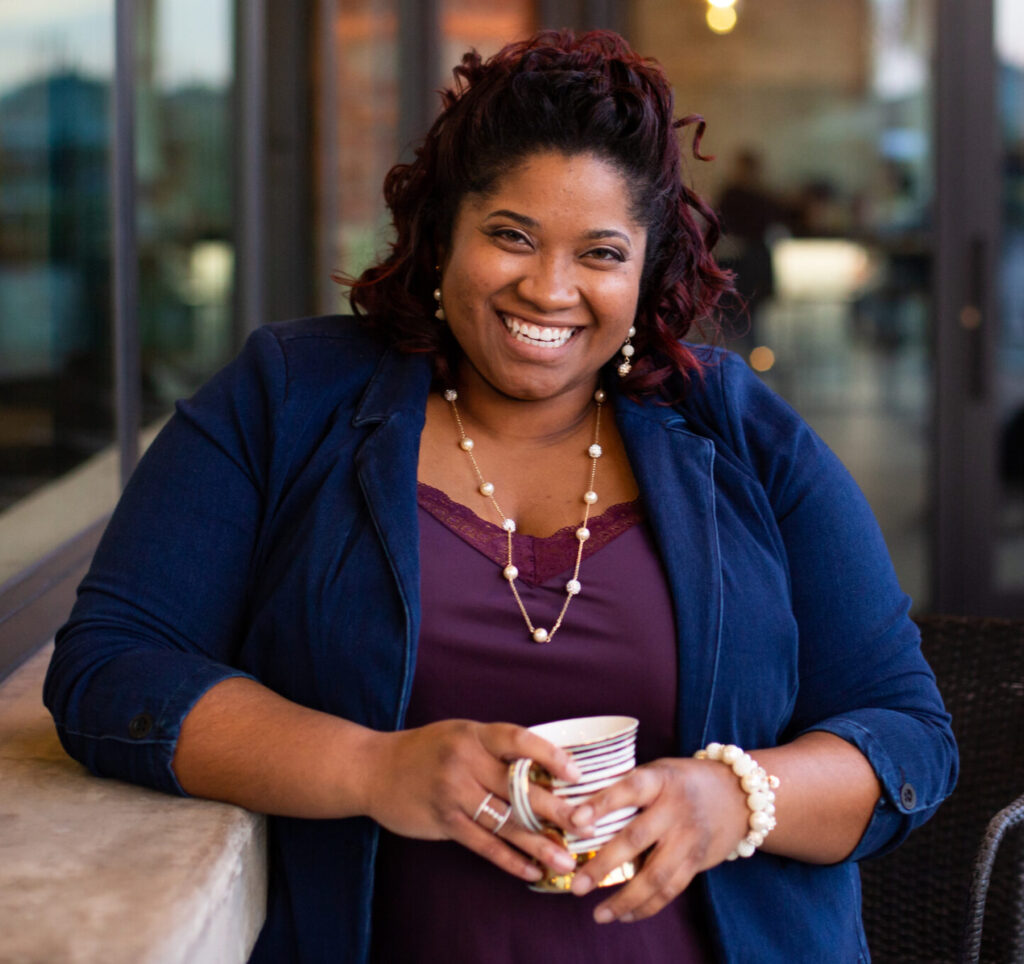 A headshot of De'Nicea Hilton, DOM, AP. She is a black woman with chin-length black curls. She is smiling wide, is wearing a blue blazer, a purple tank top, a thinly-cheined white pearl necklace, and long silver earrings. She is holding a mug in front of her using both hands.