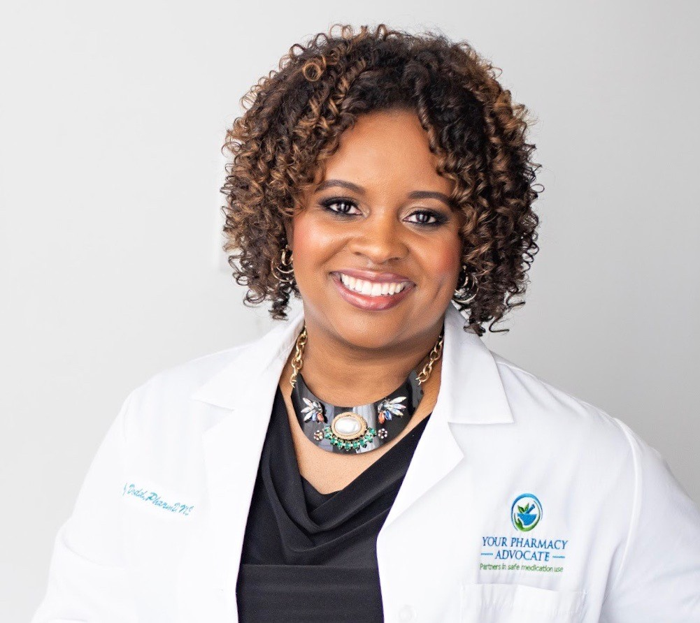 A headshot of Dr. Jerrica Dodd. She is a smiling Black woman with curly brownish-black hair that stops at her chin. She is wearing a white lab coat, a bloack tapering top, and a bold, silver necklace.