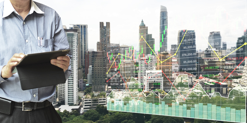 Businessman  standing and operate tablet to control and connect big data of real estate sector stock market index with chart and graph background.