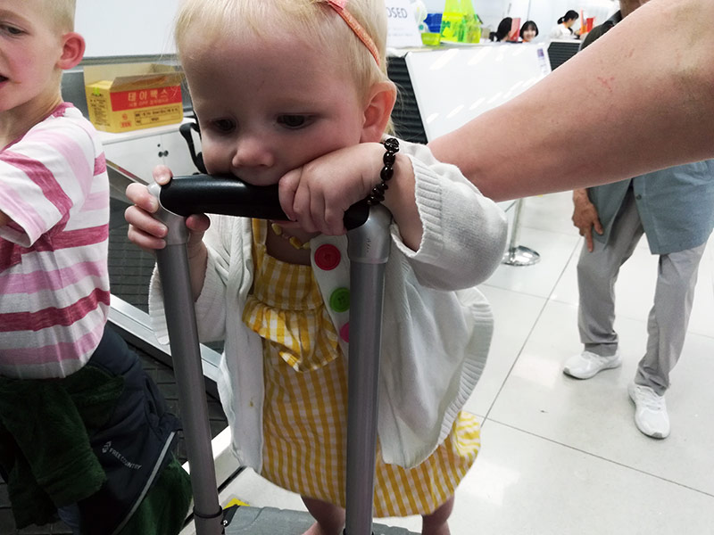 Baby Chewing on Handle of Chester Luggage