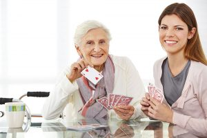 nurse and senior woman playing cards