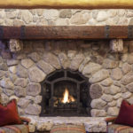 dark reclaimed wood mantel above stone fireplace by Manomin Resawn Timbers