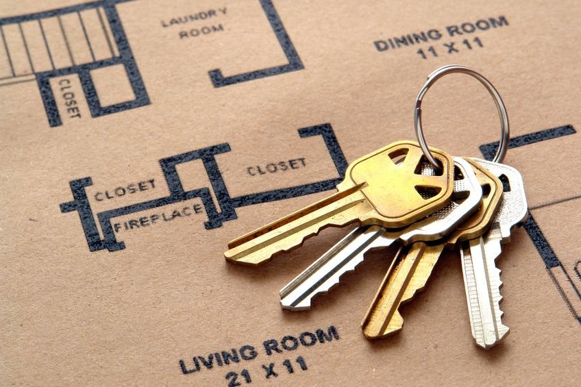 10136617 - set of house keys on a key ring over real estate home construction builder architectural floor plan printed on brown recycled paper