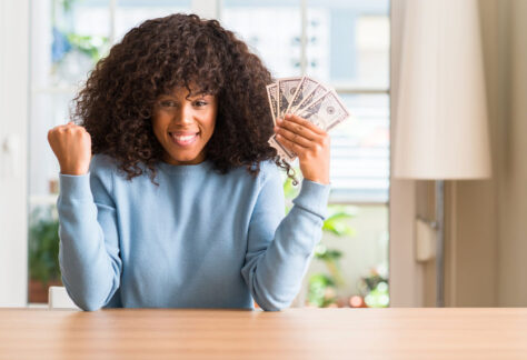 African american woman holding dollar bank notes screaming proud and celebrating victory and success very excited, cheering emotion