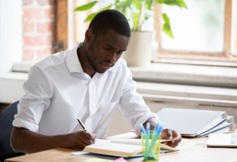 Serious african american man university student studying reading textbook making notes, focused black guy doing literature research assignment learning with book writing essay sitting at desk