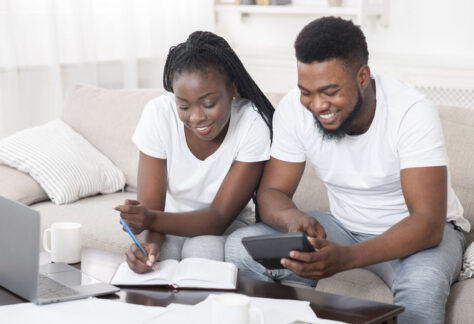 Young happy african american couple planning family budget together, sitting on sofa at home, using calculator and taking notes